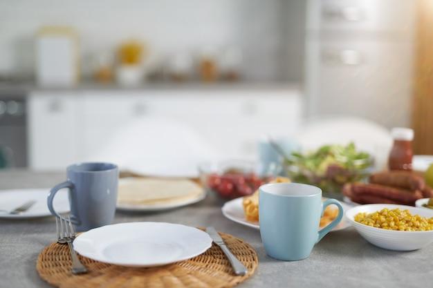 Primo piano di piatto e tazze con colazione latino-americana sul tavolo all'interno della cucina moderna. mangiare sano, mattina, concetto di idee per la colazione. messa a fuoco selettiva