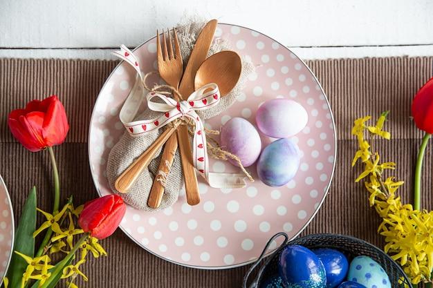 Primo piano del piatto con posate, uova di pasqua e fiori vista dall'alto.