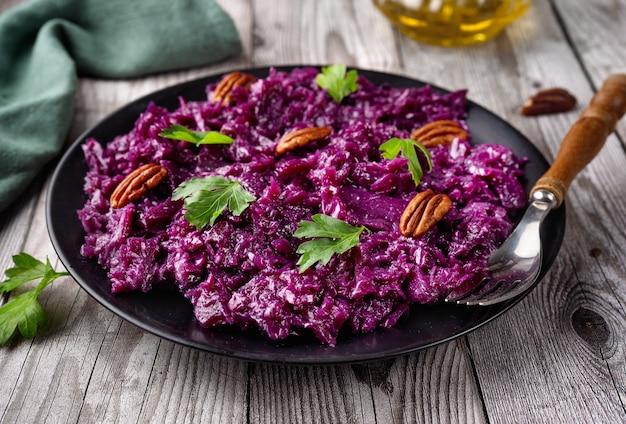 Primo piano di un piatto con insalata di cavolo rosso vegano sano sul tavolo rustico grigio