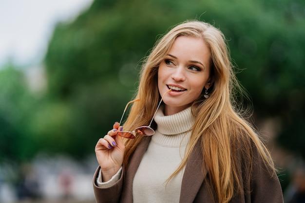 Primo piano di una giovane donna giocosa rossa vestita di maglione bianco e cappotto beige