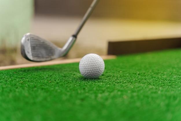 Primo piano che gioca nel mini-golf sull'erba verde usando niblick