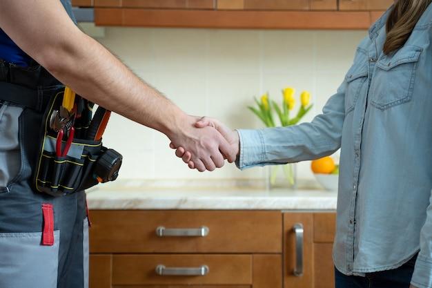 Chiuda in su dell'idraulico e del cliente che agitano le mani nel riparatore della cucina che agitano le mani con la donna