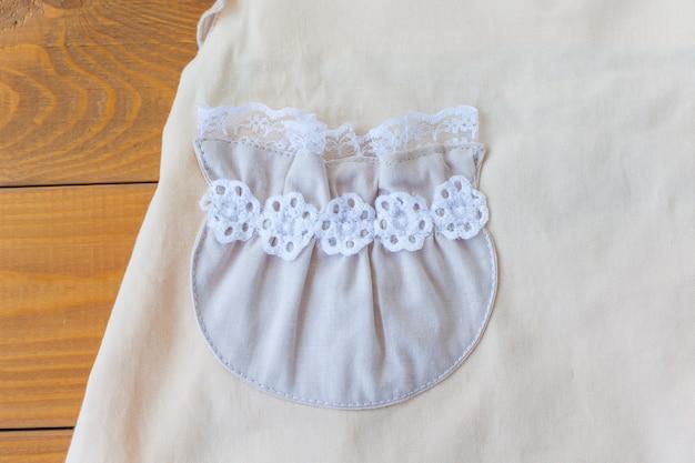 Primo piano della tasca di un vestito per bambini beige con dettagli del tessuto dell'abbigliamento. abito in cotone per bambina.