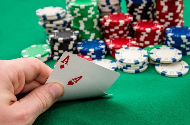 Primo piano di un giocatore di poker in possesso di carte da gioco.