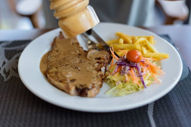 Il pepe nero della bistecca di braciola di maiale del primo piano con gli uomini passa e salsa di pepe nero in disco bianco