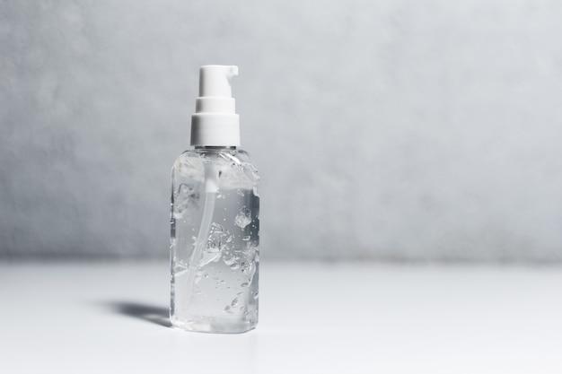 Primo piano della bottiglia di plastica portatile con gel antisettico disinfettante sul tavolo bianco. superficie della parete strutturata grigia.