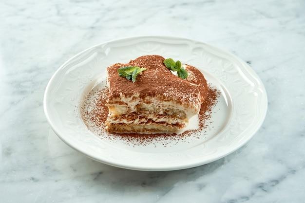 Primo piano su una porzione di dessert italiano tiramisù gourmet servito in un piatto bianco su un tavolo di marmo