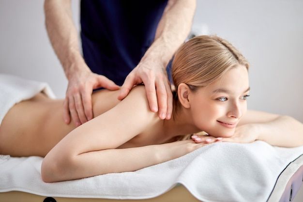 Ritratto ravvicinato di adorabile femmina caucasica sdraiata sul divano che riceve un massaggio, guardando il lato in contemplazione, sorridendo in modo carino. donna a torso nudo sdraiata sulla pancia
