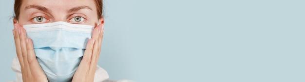 Close up ritratto di adulto infermiere o medico che indossa la maschera protettiva medica con le mani su sfondo blu