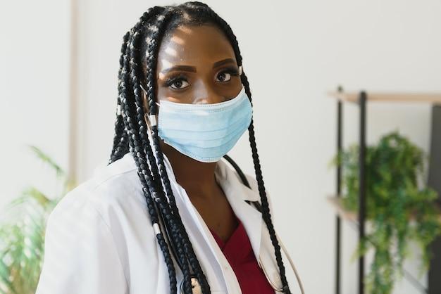 Chiuda sul ritratto dello specialista sanitario femminile felice afroamericano nella mascherina medica.