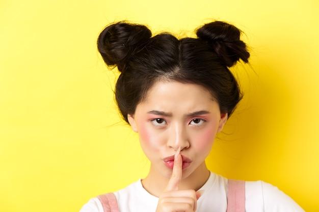Chiuda sul ritratto della ragazza asiatica arrabbiata che zittisce, preme le dita sulle labbra e dì di essere tranquillo, rimproverando la persona forte, ha bisogno di silenzio, racconta un grande segreto, in piedi sul giallo