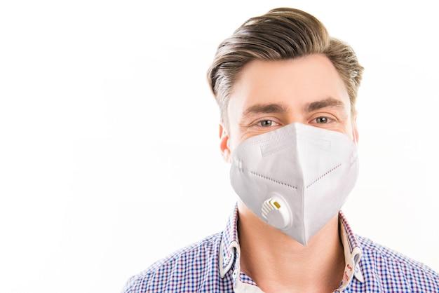 Ritratto ravvicinato di un ragazzo biondo attraente che indossa una maschera moderna riutilizzabile arresta la malattia del patogeno respiratorio cov mers ncov-2 isolato su sfondo di colore bianco