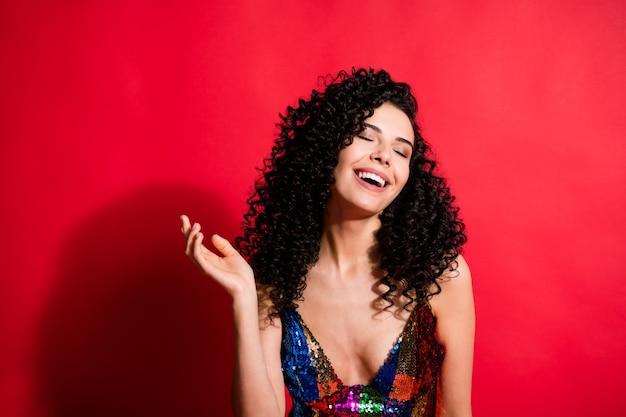 Ritratto ravvicinato di una ragazza dai capelli ondulati allegra sognante e attraente che si gode la festa divertendosi isolata su uno sfondo di colore rosso vivo