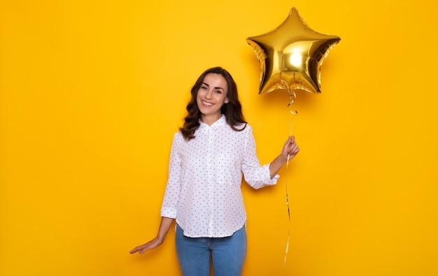 Ritratto ravvicinato di un'attraente donna moderna mentre posa con un palloncino a forma di stella in mano e celebra qualcosa