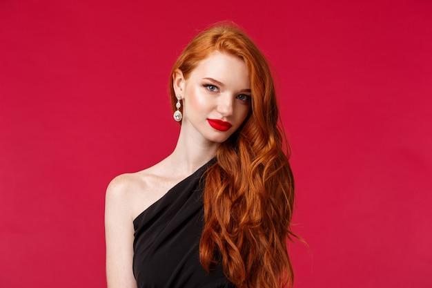 Ritratto di close-up di attraente giovane donna sensuale e civettuola con rossetto rosso, catturare lo sguardo, indossare orecchini e abito nero, guardare impertinente sa cosa vuole, muro rosso
