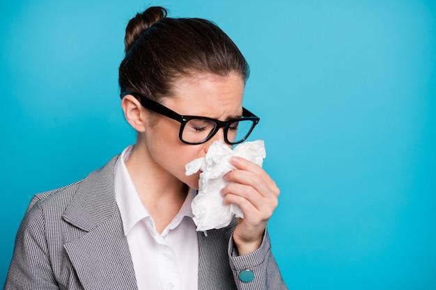 Ritratto ravvicinato di un'attraente insegnante malata che piange starnutisce e si sente male isolata su uno sfondo di colore blu vibrante