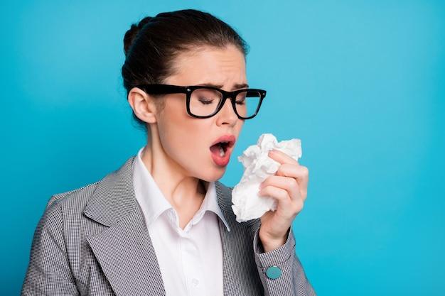 Ritratto ravvicinato di un'attraente insegnante malata che starnutisce con l'influenza usando un tovagliolo isolato su uno sfondo di colore blu brillante
