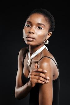 Ritratto ravvicinato di una giovane donna attraente che guarda la parte anteriore isolata sul muro nero