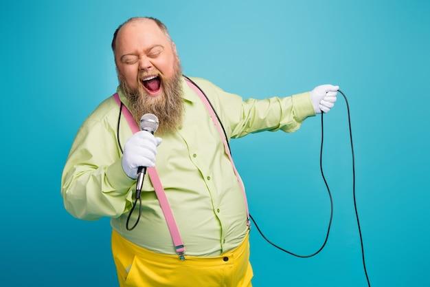 Ritratto del primo piano dell'uomo anziano barbuto che canta il karaoke