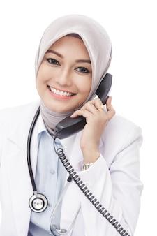 Chiuda sul ritratto di bello medico femminile asiatico che parla sul telefono