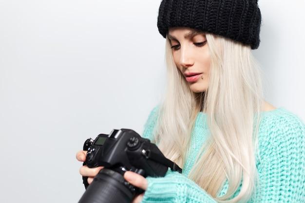 Ritratto ravvicinato di una bella ragazza bionda fotografa che guarda la fotocamera dslr
