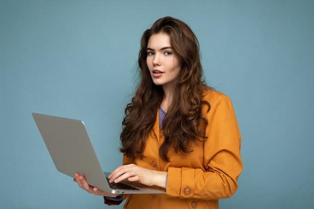 Ritratto del primo piano di bella brunet riccia giovane donna che tiene computer netbook indossa giacca gialla digitando sulla tastiera isolata sulla parete blu.