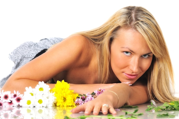 Ritratto del primo piano di una bellissima giovane donna bionda femminile in posa con mazzi di fiori su un bianco in studio