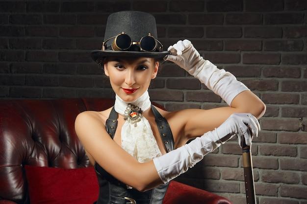 Ritratto del primo piano di una bella ragazza steampunk in lingerie e calze che si siede nella vecchia poltrona.