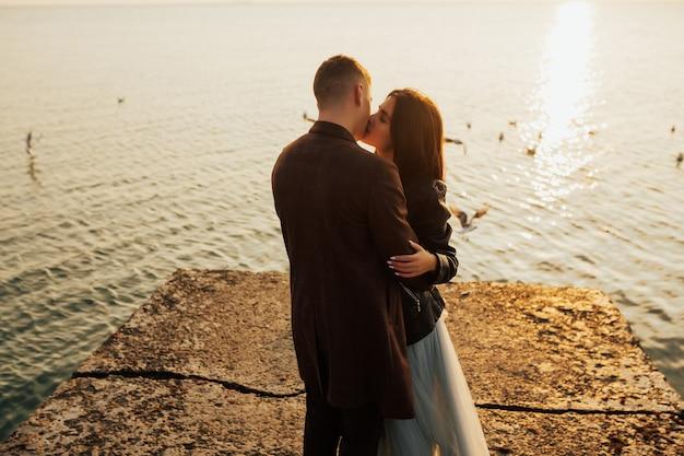 Chiuda sul ritratto di una bella giovane coppia elegante innamorata in piedi e si baciano sulla spiaggia al tramonto.