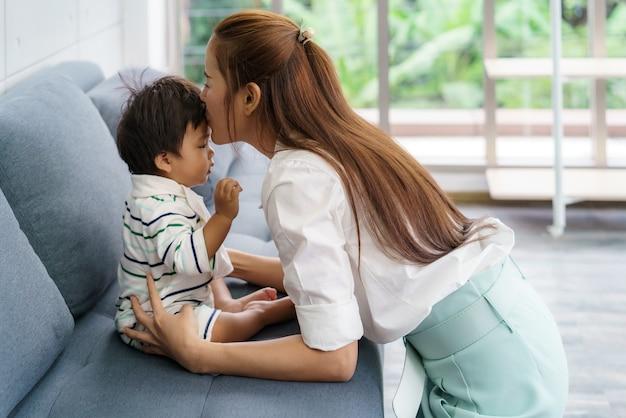 Chiuda sul ritratto di bella giovane madre asiatica che bacia il suo bambino appena nato per amare il concetto di giorno della madre di stile di vita della donna dell'asia con lo spazio della copia.