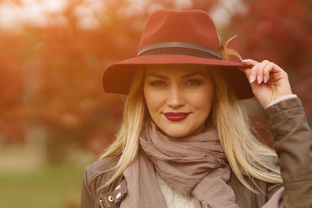 Ritratto del primo piano di bella giovane bionda con trucco e manicure in cappello bordeaux con piuma e sciarpa sullo sfondo del parco autunnale sfocato soleggiato, luce solare