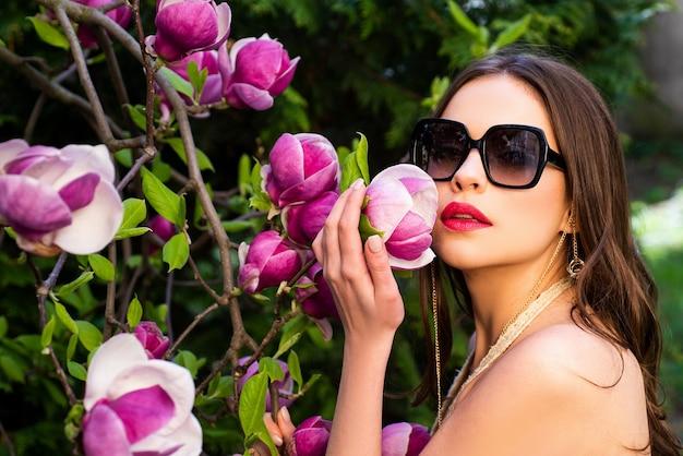 Primo piano ritratto di bella giovane donna bruna con labbra rosse e pelle sana con fiori rosa...