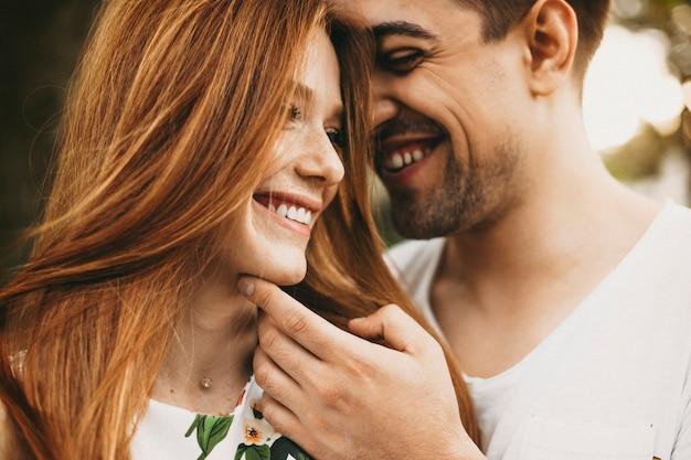 Chiuda sul ritratto di una bella giovane coppia caucasica divertendosi a sorridere mentre l'uomo sta toccando il viso delle sue amiche mentre lei guarda lontano sorridendo.
