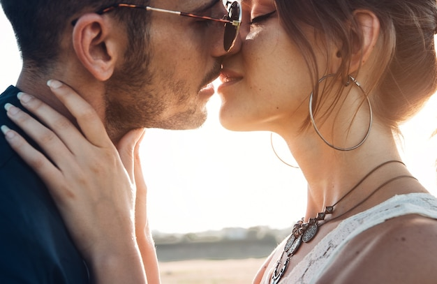 Close up ritratto di una giovane e bella coppia in attesa di baciare al tramonto.