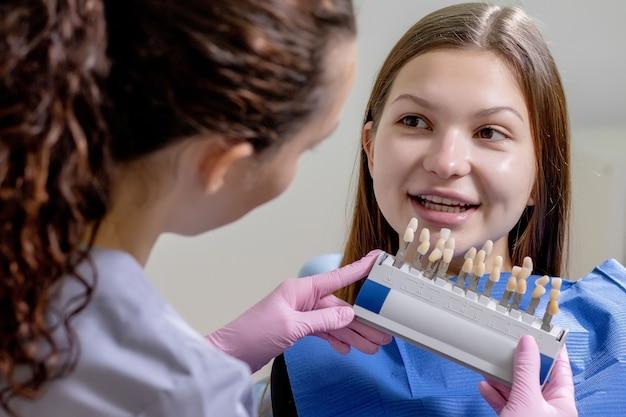 Close up ritratto di bella giovane donna seduta in poltrona odontoiatrica mentre stomatologo mani in guanti sterili che tengono campioni di dente