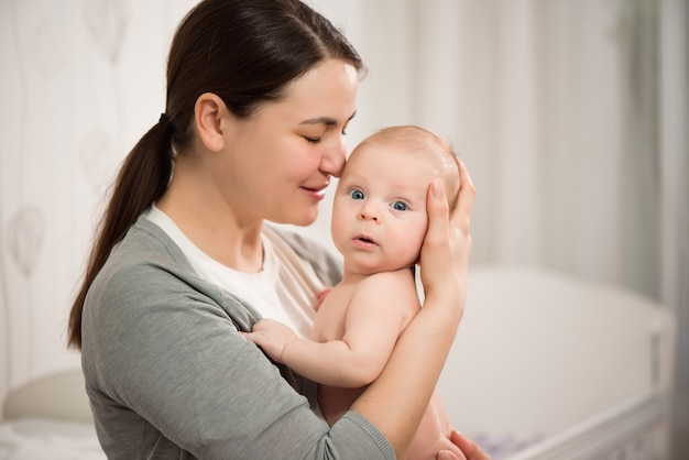 Chiuda sul ritratto di bella giovane ragazza madre che bacia il suo neonato.