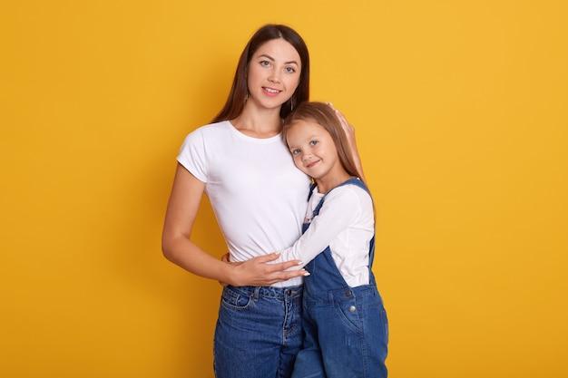 Chiuda sul ritratto di bella giovane madre con la piccola posa graziosa della figlia isolata sopra giallo