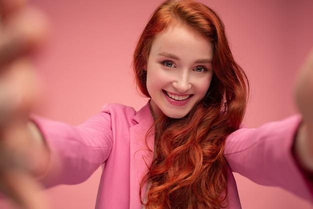 Ritratto del primo piano di bella giovane donna della testarossa che fa selfie usando due mani.