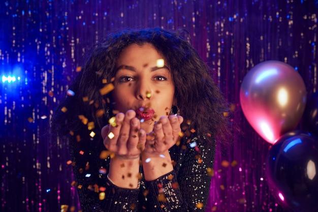 Chiuda sul ritratto di giovane e bella donna che soffia glitter in telecamera mentre si gode la festa in discoteca, copia dello spazio