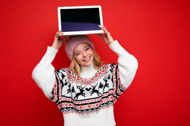 Ritratto ravvicinato di una bella giovane donna che tiene in mano un computer portatile con un monitor vuoto