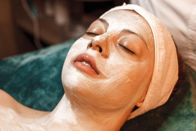 Close up ritratto di una giovane e bella donna che riposa pur avendo una maschera bianca per la cura della pelle sul viso in un centro termale e benessere.