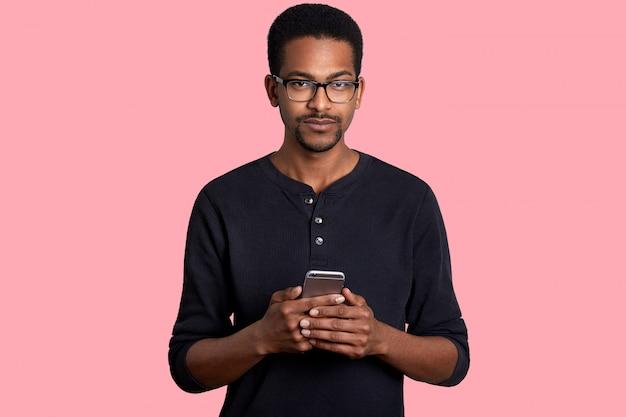 Chiuda sul ritratto di un uomo di colore con i capelli corti e ricci, la piccola barba, tiene lo smart phone in mano, scrive il massaggio agli amici, vestito in abito casual, isolato sul muro bianco.
