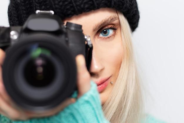 Ritratto del primo piano del fotografo della ragazza bionda che prende foto sulla macchina fotografica di dslr.