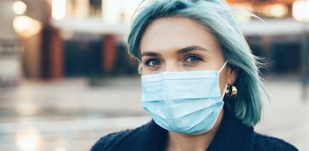 Chiuda sul ritratto della donna caucasica dai capelli blu che indossa la maschera antinfluenzale speciale mentre