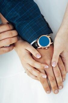 Ritratto del primo piano della sposa e dello sposo. fedi nuziali sulle loro mani