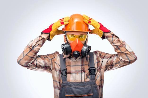Ritratto del primo piano di un costruttore con occhiali protettivi, respiratore e casco al chiuso. equipaggiamento per la protezione personale.
