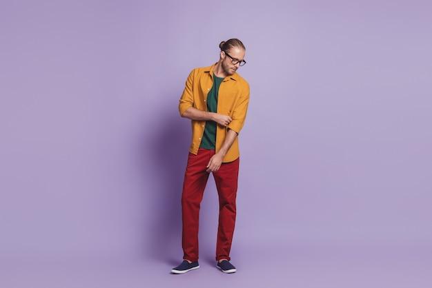Ritratto ravvicinato di un uomo d'affari che posa le tasche delle mani sul muro viola