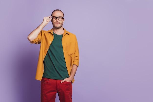 Ritratto ravvicinato di un uomo d'affari positivo con le dita degli occhiali sulla parete viola