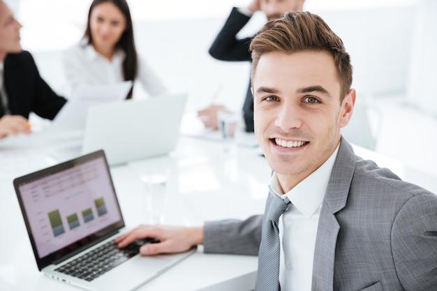 Ritratto ravvicinato di un uomo d'affari seduto con il computer portatile al tavolo in ufficio con i colleghi e guardando la telecamera