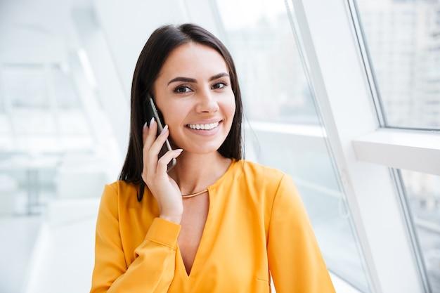Ritratto ravvicinato di una donna d'affari con una camicia arancione in piedi vicino alla finestra e che parla al telefono